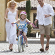 Family WIth Girl Riding Bike & Happy Parents — Stock Photo