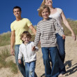 Mother, Father and Two Boys Walking Having Fun At Beach - Stock Photo