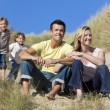 Family Sitting on Beach Having Fun - Stock Photo