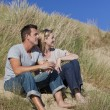 Stock Photo: Romantic Man and Woman Couple Sitting Together On A Beach