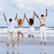 Four Young , Two Couples, Jumping in Celebration On Beach — Stock Photo #6478823