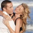 Man and Woman Couple In Romantic Embrace On A Beach - Stock Photo