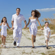 Stock Photo: Mother, Father and Children Family Running Having Fun At Beach