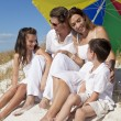 Family Laughing Under Colorful Umbrella On Beach — Stock Photo