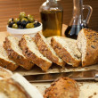 Sliced Rustic Bread, Olive Oil, Stuffed Green &amp; Black Olives - Stock Photo