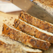 Close up of Slicing Rustic Wholemeal Seeded Loaf of Bread — Stock Photo