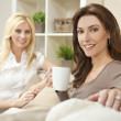 Two Beautiful Women Friends Drinking Tea or Coffee at Home — Stockfoto