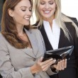 Two Happy Businesswomen Using a Tablet Computer — Stock Photo #6479845
