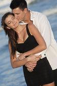 Man och kvinna par kyssas i romantiska famn på stranden — Stockfoto