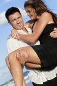 Couple romantique sur la plage avec l'homme portant sa femmecouple homme et femme dans une étreinte romantique sur la plage — Photo