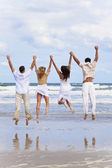 Four Young , Two Couples, Jumping in Celebration On Beach — Stock Photo