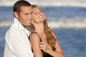 Man and Woman Couple Laughing In Romantic Embrace On Beach — Stock Photo