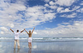 Man and Woman Couple Celebrating Arms Raised On A Beach — Stock Photo