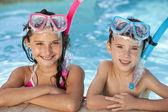 Jongen en meisje in zwembad met bril en snorkel — Stockfoto