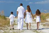 Moeder, vader en kinderen familie wandelen op het strand — Stockfoto