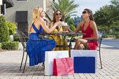 Trzy piękne młode kobiety filiżankę kawy z torby na zakupy — Zdjęcie stockowe