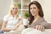 Two Beautiful Women Friends Drinking Tea or Coffee at Home — Stock Photo