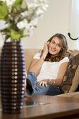 Cep telefonunu evde üzerinde çekici genç kadın — Stok fotoğraf