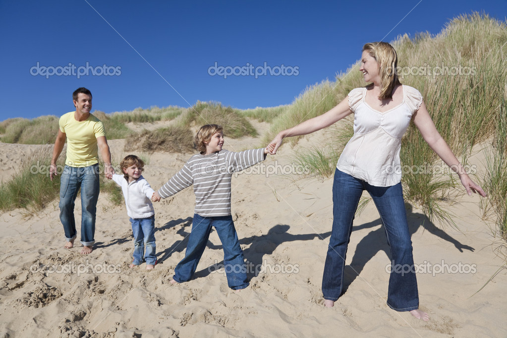 A happy family of mother, father and two sons, walking holding hands and having fun in the sand dunes of a sunny beach — Stock Photo #6470148
