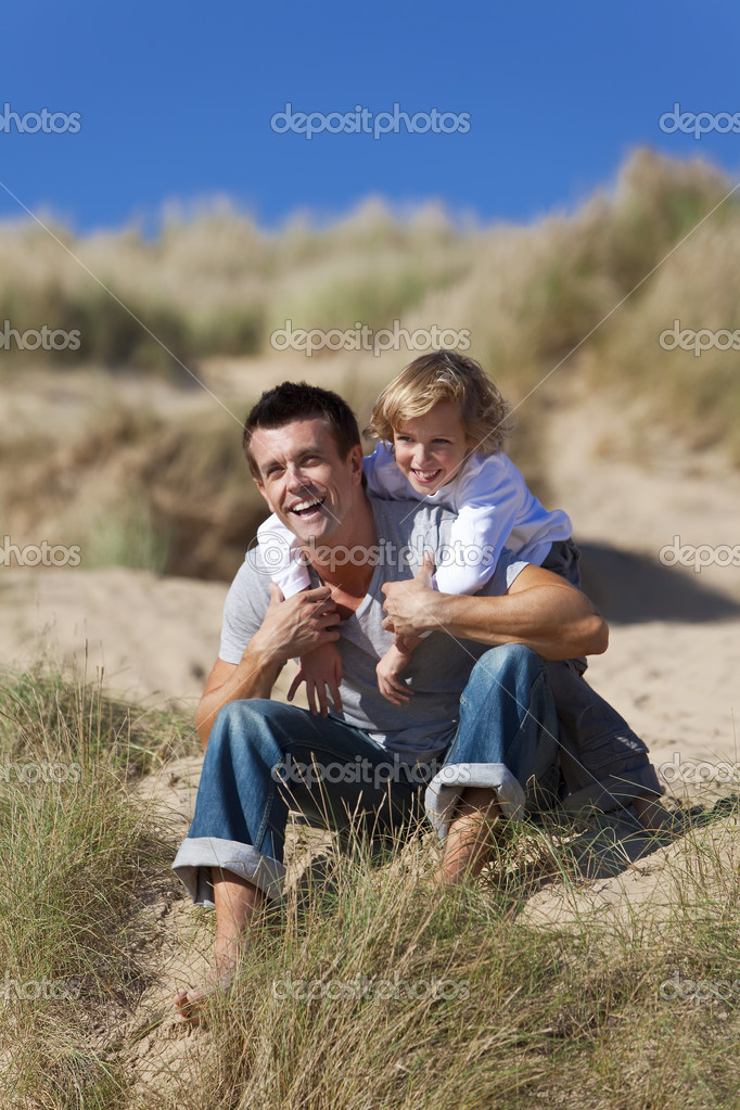 A man and young boy, father and son, sitting down, laughing and having fun in the sand dunes of a sunny beach — Stock Photo #6470150
