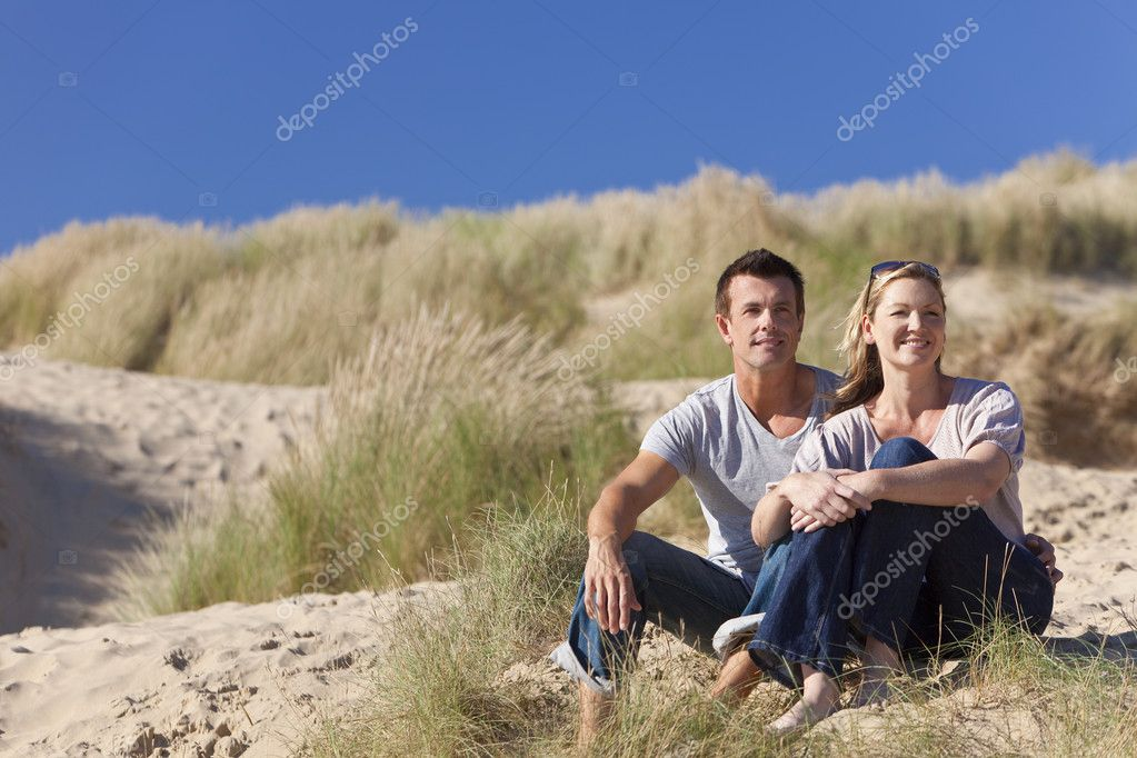 A romantic young man and woman couple sitting together in the sand dunes of a sunny beach with a bright blue sky — Stock Photo #6470157
