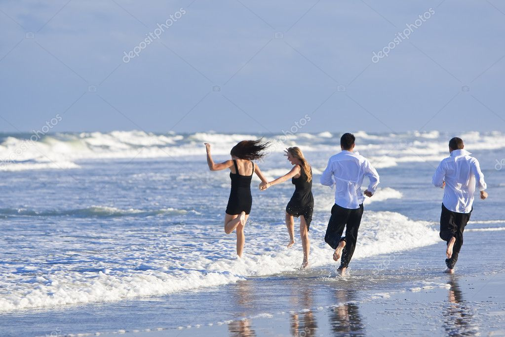 Four young , two couples, having fun and running into the sea on a beach — Stock Photo #6478820