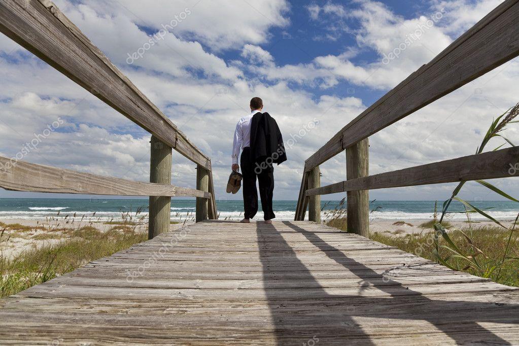 homme d 39 affaires debout pieds nus la recherche sur une plage la mer photographie dmbaker. Black Bedroom Furniture Sets. Home Design Ideas