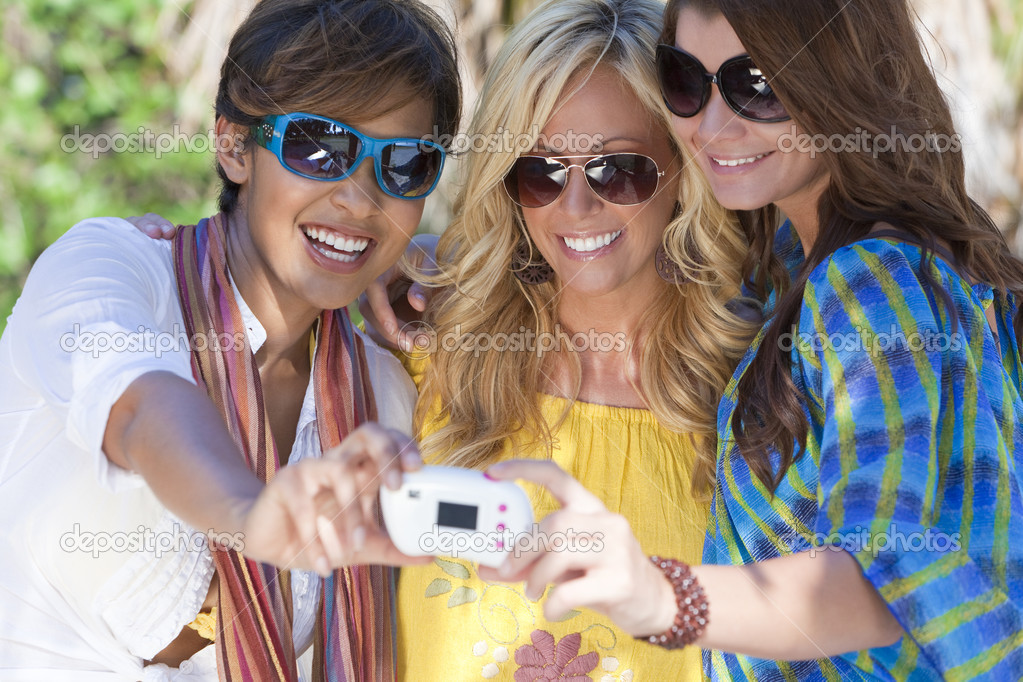 Three beautiful young women in their twenties laughing and having fun taking pictures of themselves using a digital camera while on vacation in a tropical resor — Stock Photo #6479794