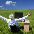 Businessman Celebrating Arms Raised At Desk In Green Field — Stock fotografie