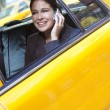 Young Woman Talking on Cell Phone in Yellow Taxi — Stok fotoğraf