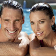 beautiful couple relaxing in swimming pool with perfect smiles — Stock Photo #6485627