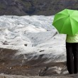 Stock Photo: Environmental Concept Of A Woman With Green Umbrella By Glacier