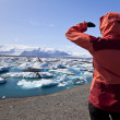 Foto Stock: Female Hiker Looking at Iceberg Filled Lagoon, Jokulsarlon, Icel
