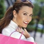 mooie gelukkig vrouw met roze en witte shopping tassen — Stockfoto