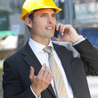 Stock Photo: Man In Industrial Hard Hat and Talking On Cell Phone
