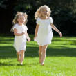 Two Pretty Young Girls Running Through A Sunlit Green Park — Stock Photo #6486971