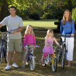 Happy Family Riding Bikes In A Park — Stock Photo