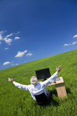 Businessman Celebrating Arms Raised At Desk In Green Field — Stock Photo