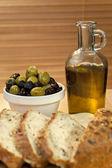 Aceite de oliva, aceitunas verdes y negras rellenas y pan rústico — Foto de Stock