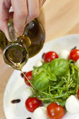 Olive Oil Dressing on Tomato Mozzarella Rocket & Basil Salad — Stock Photo