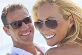Couple heureux séduisante femme et homme en lunettes de soleil à la plage — Photo