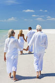 Two Couples Generations of Family Holding Hands on Tropical Beac — Stock Photo
