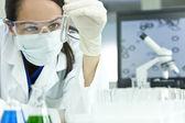 Médico científico o mujer femenina con tubo de ensayo en laboratorio — Foto de Stock