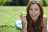 Beautiful Woman Outside Eating An Apple and Smiling — Stock Photo