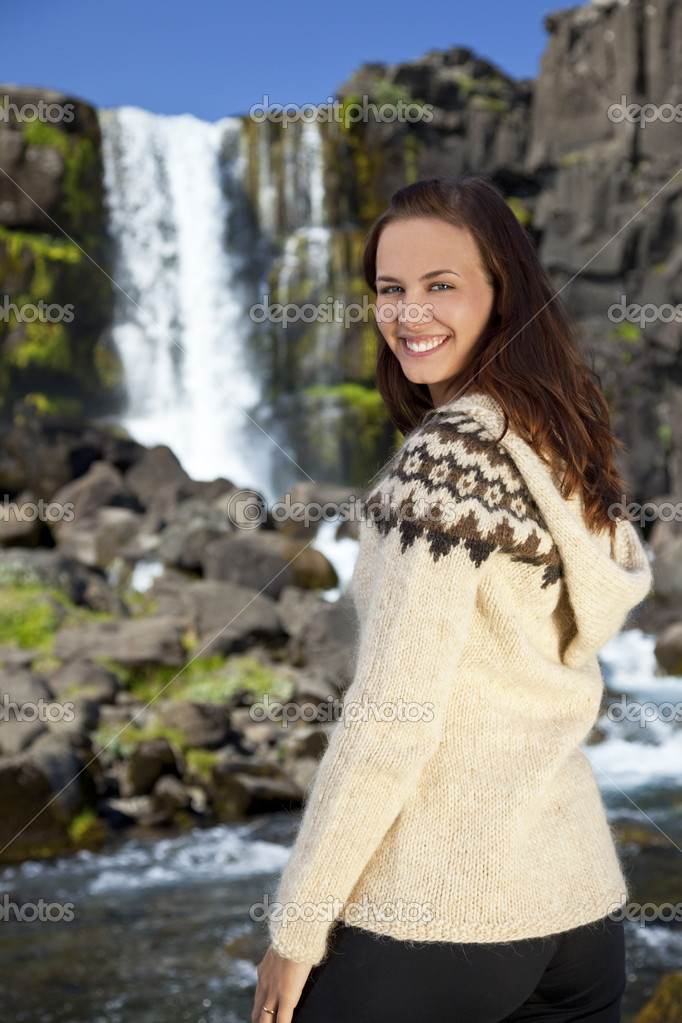 A beautiful Scandinavian woman wearing traditionally patterned knitwear smiling in front of a mountain waterfall. Shot on location in Iceland. — Stock Photo #6480147