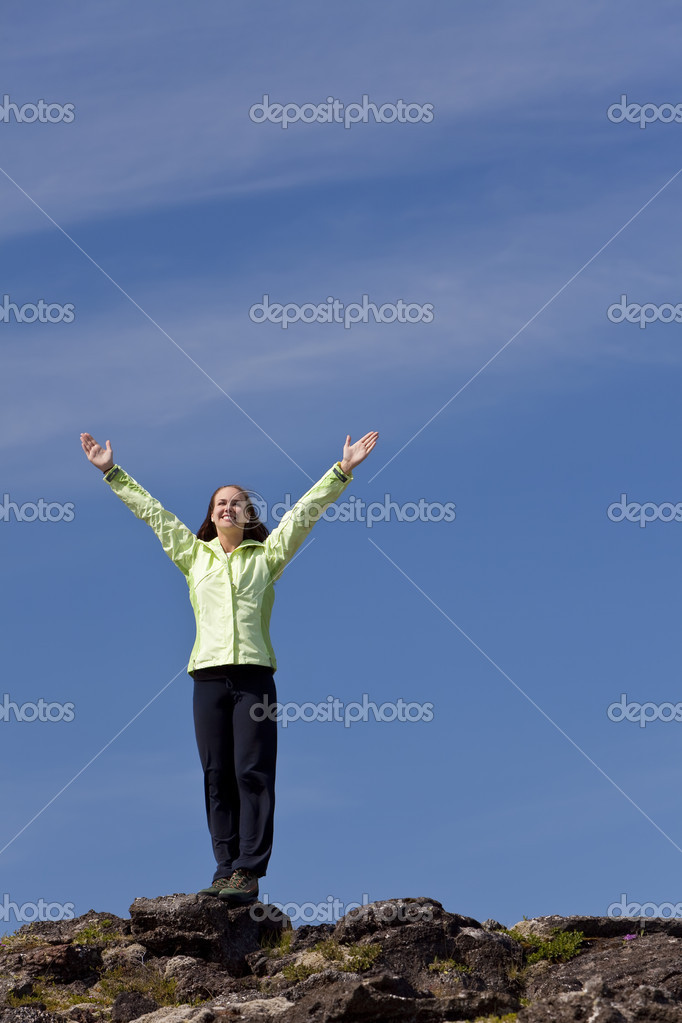 A beautiful young woman stands on the horizon arms raised celebrating reaching the top of a mountain.  Stock Photo #6480212