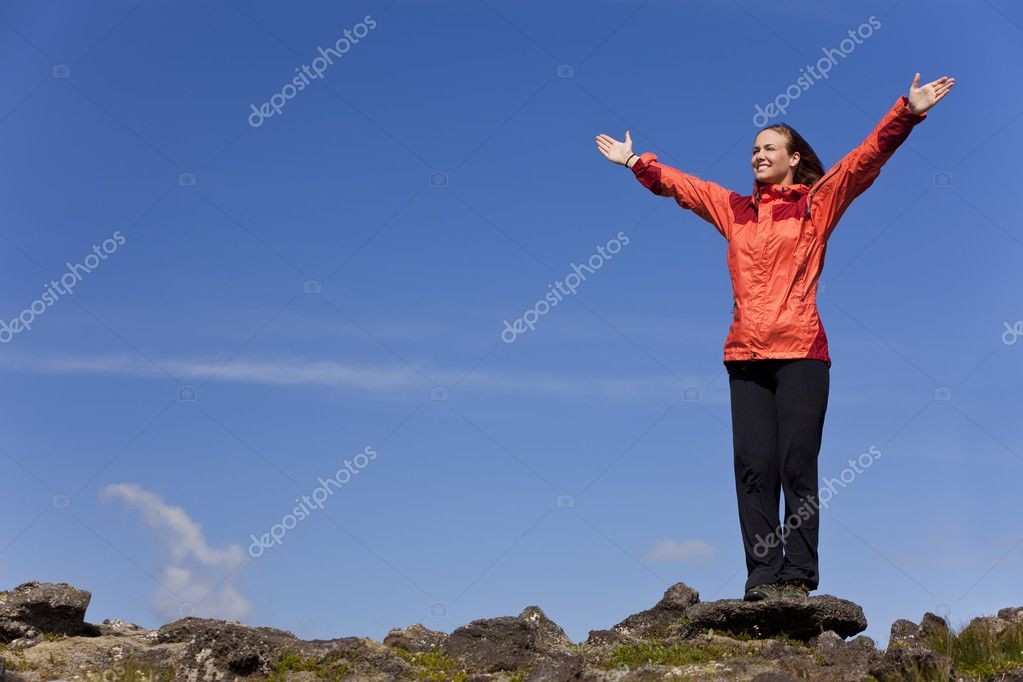 A beautiful young woman stands on the horizon arms raised celebrating reaching the top of a mountain. — Stock Photo #6480214