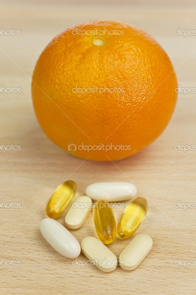 An orange and tablets either medicinal pills or nutritional vitamin supplements.   Stock Photo #6481953
