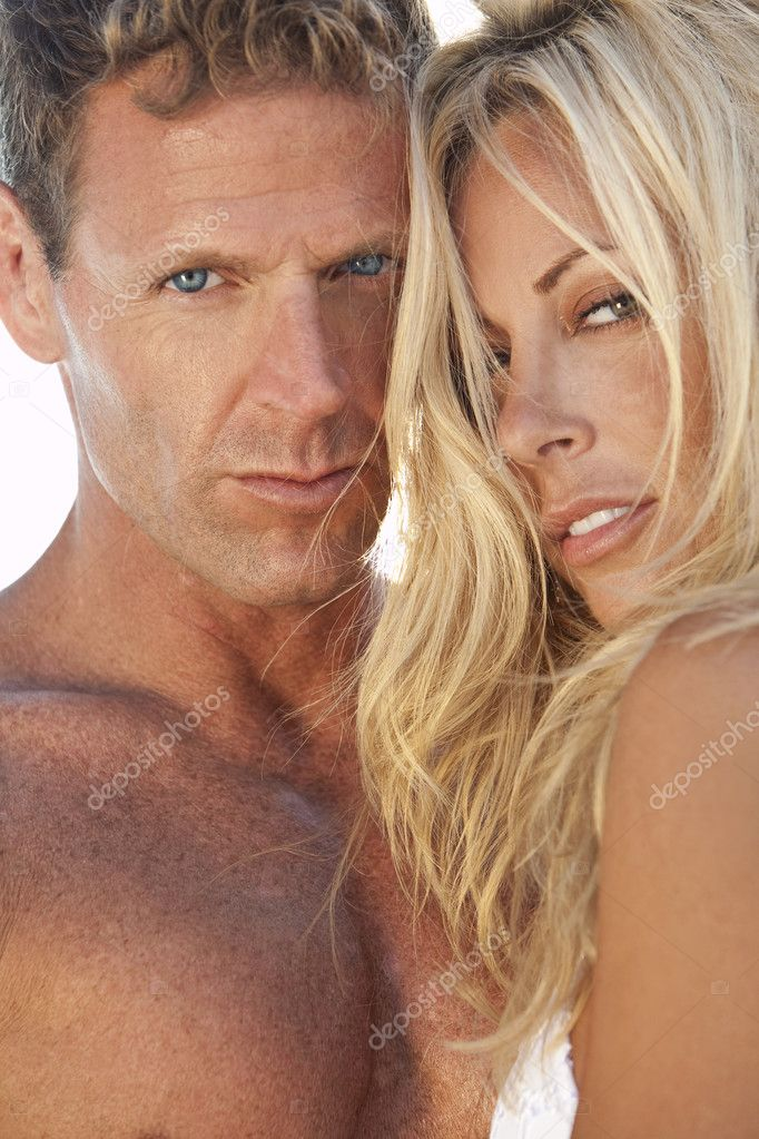 A sexy and attractive man and woman couple in the sunshine at the beach