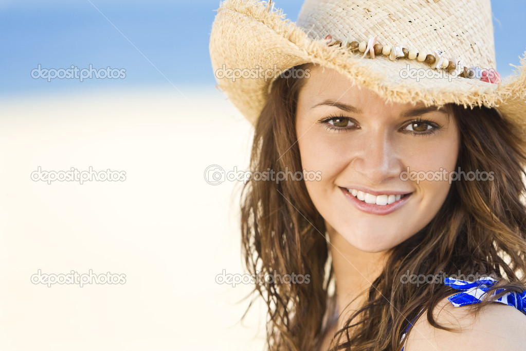 A sexy and beautiful young brunette woman sitting at the beach wearing a straw cowboy hat with golden sand and the sea behind her — Stock Photo #6484389